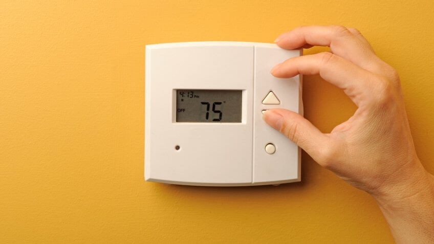 A woman turns down the thermostat.