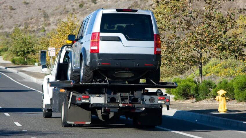A tow truck towing a silver suv.