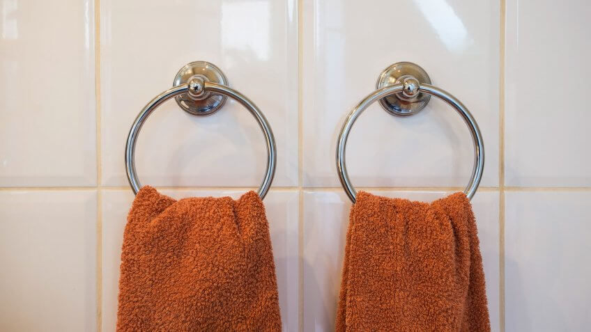 White hand towel hanging on hanger in toilet bathroom for cleaning and drying hand.