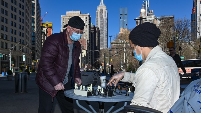 "Two men, who identified themselves as ""Big Jay' and ""The Genius"", wear protective masks and gloves while playing a game of chess in the Flat Iron District of New York."