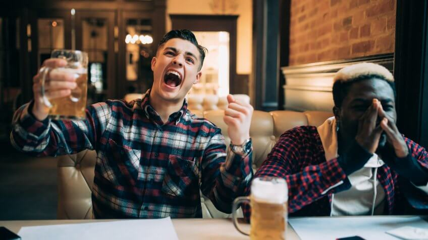two men watch sports at bar