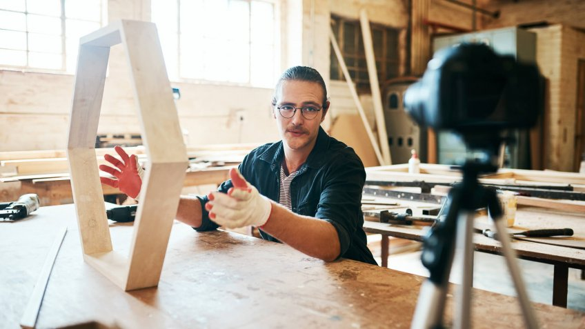 Shot of young carpenter recording a tutorial of him making a wooden masterpiece on a video camera inside his workshop.