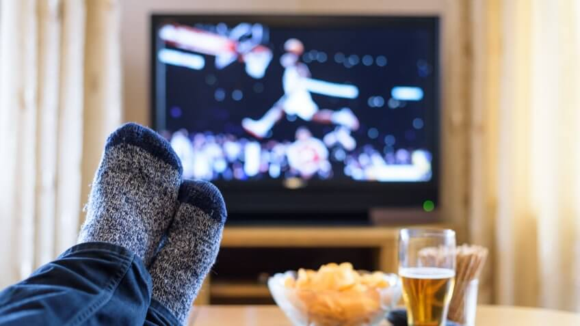 Television, TV watching (basketball game) with feet on table eating snacks and drinking beer - stock photo.
