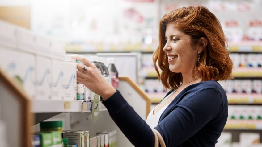 Shot of a young woman browsing through products in a pharmacy.