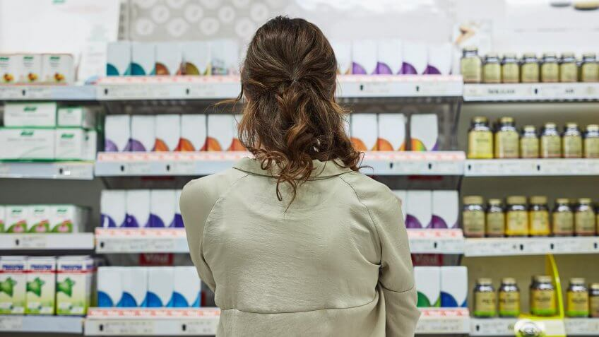 Rearview shot of a young woman browsing the shelves of a pharmacy.