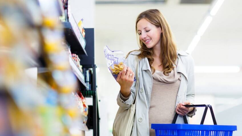 Beautiful young woman shopping in a grocery store/supermarket (color toned image).