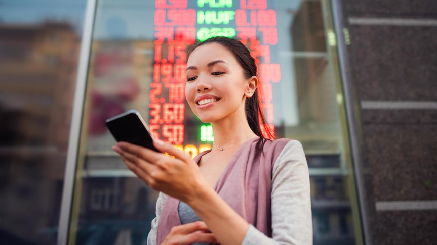 A young beautiful Asian woman using an application in her smart phone to check currency exchange rates in front of an illuminated information board.