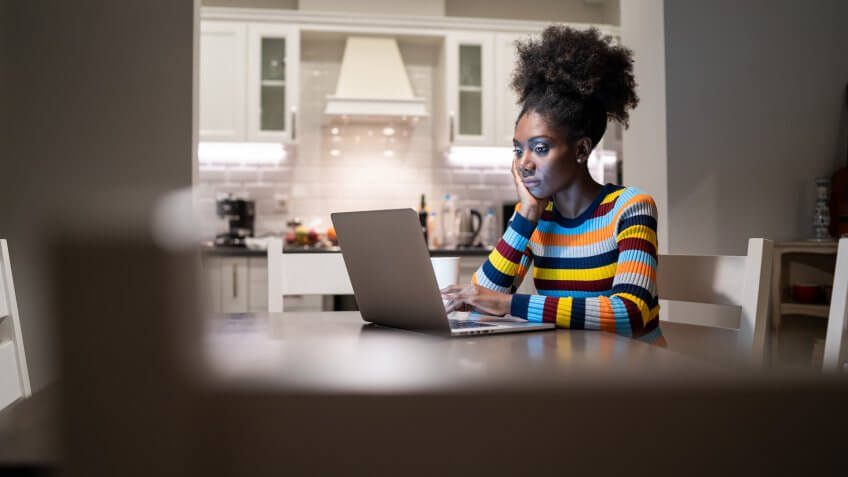 African Woman using laptop at home at night.