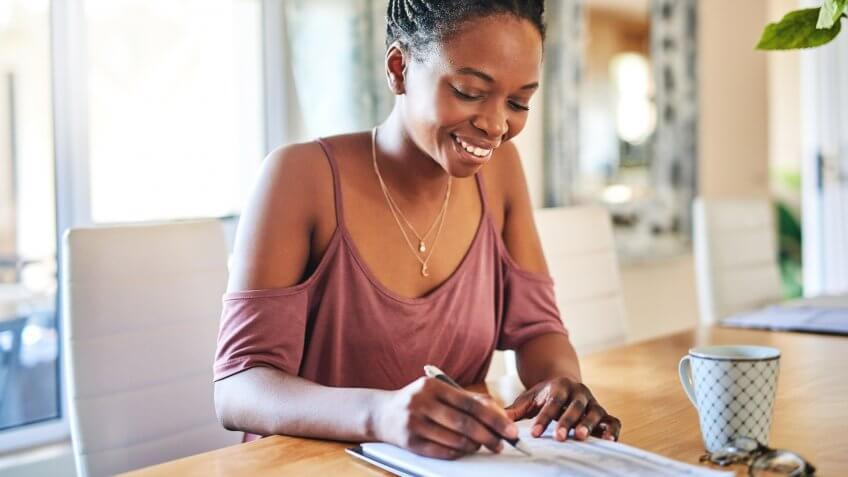 Cropped shot of a young woman filling out paperwork at home.