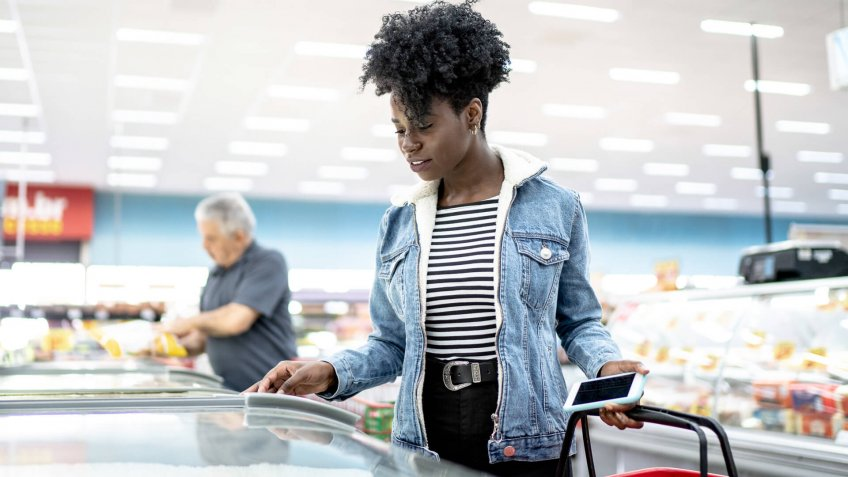 Young woman looking for products in the supermarket freezer.
