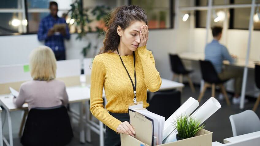 Frustrated young woman in yellow sweater standing at table and touching face with hand while packing stuff in office after dismissal.
