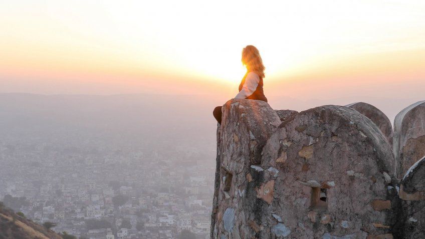 woman on cliff at sunset.