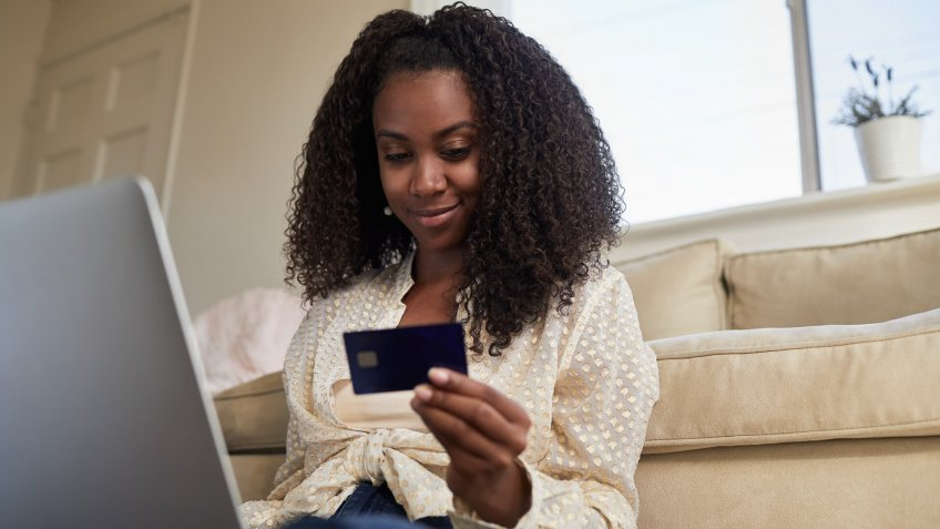 Smiling young African American woman doing some online shopping with a credit card and laptop while sitting on her living room floor.