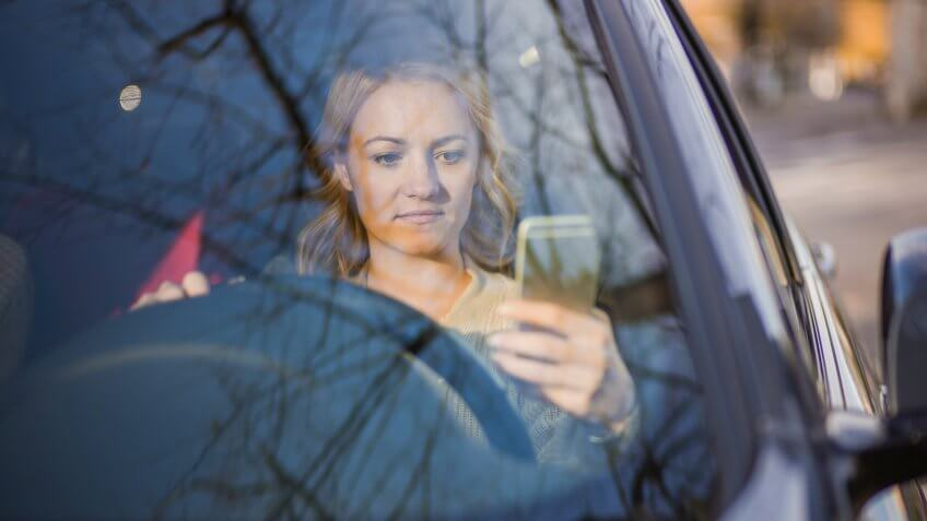 Young serious woman driving car and reading text message on cell phone.