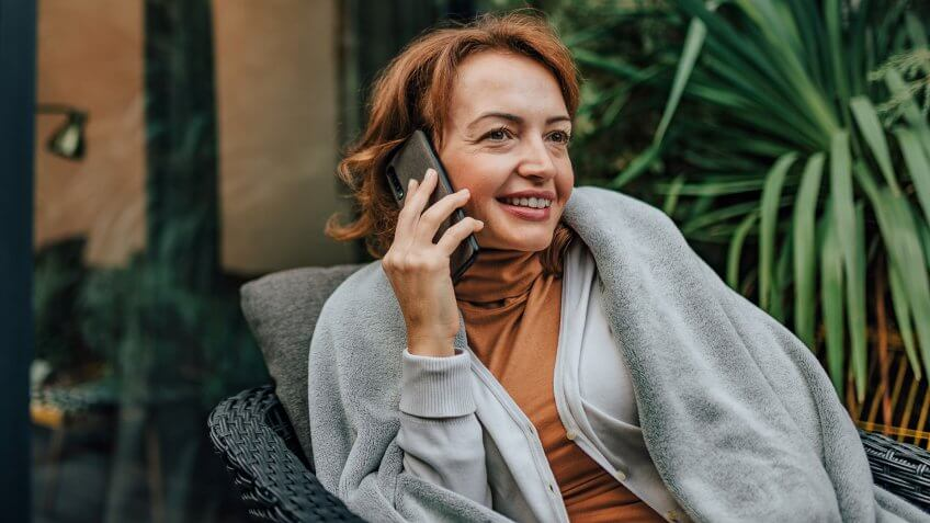 Successful woman talking on smart phone on the patio of modern house, portrait, copy space.