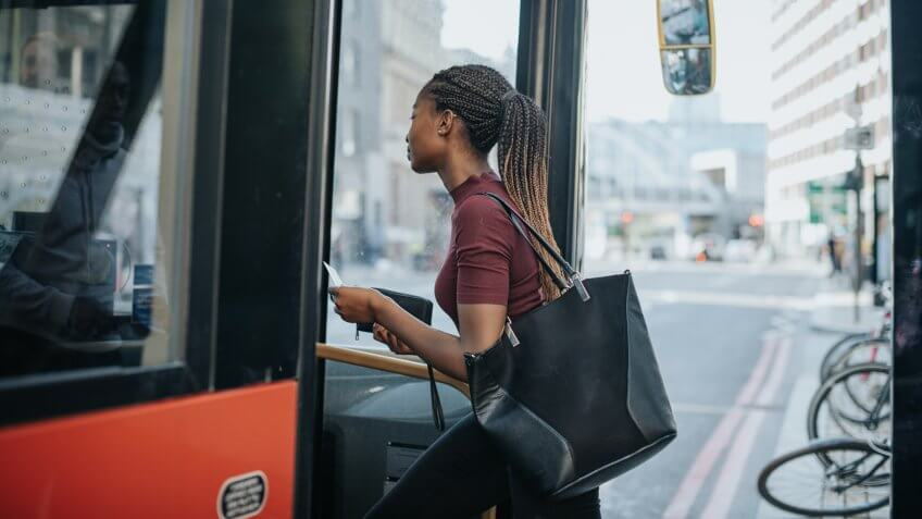 Woman getting on the bus.