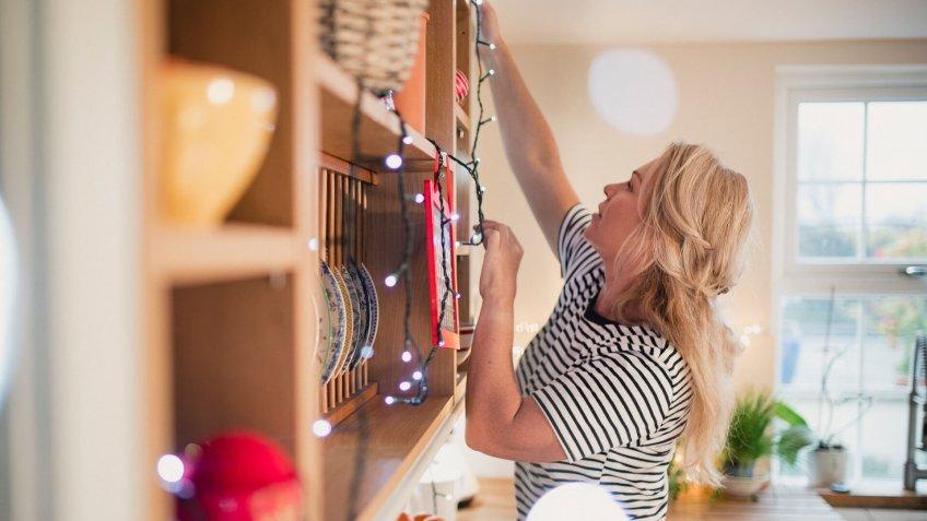 Mature woman reaching high to hang lights onto the shelves.