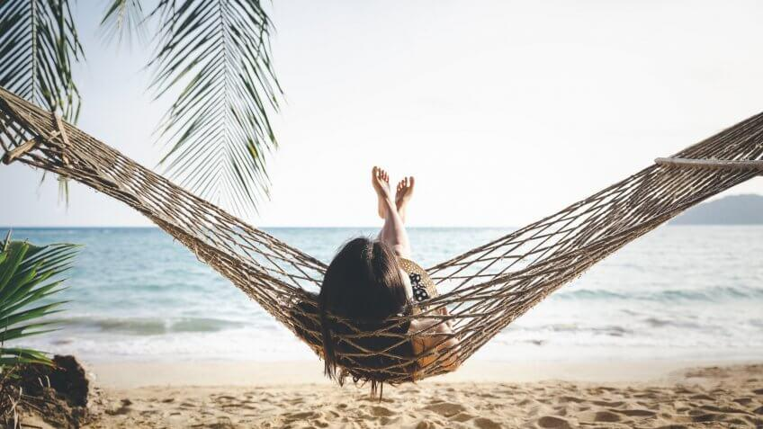 Summer vacations concept, Happy woman with white bikini, hat and shorts Jeans relaxing in hammock on tropical beach at sunset, Koh mak, Thailand.