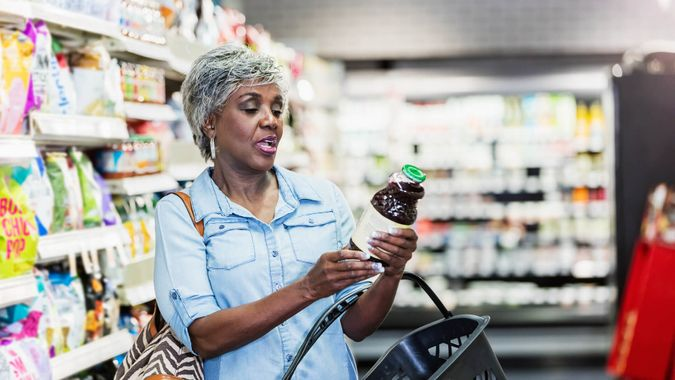 A senior African-American woman in her 60s shopping in a grocery store, carrying a shopping basket.