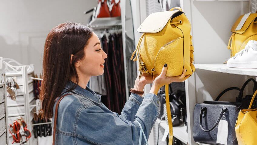 woman in shop choosing leather bags and backpacks, fashion accessories and shopping concept.