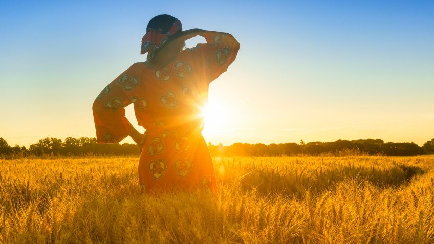 African woman in traditional clothes standing, looking, hand to eyes, in field of barley or wheat crops at sunset or sunrise.