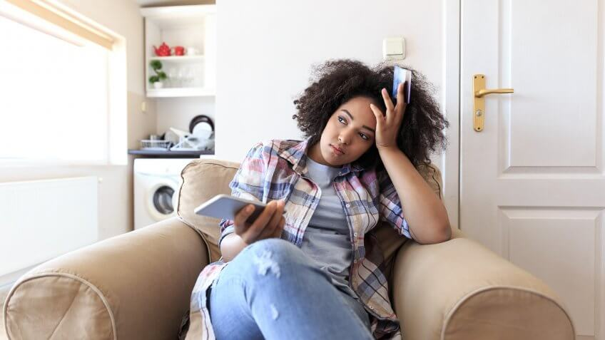 Young woman sitting at home, holding smart phone, having problems with credit card.