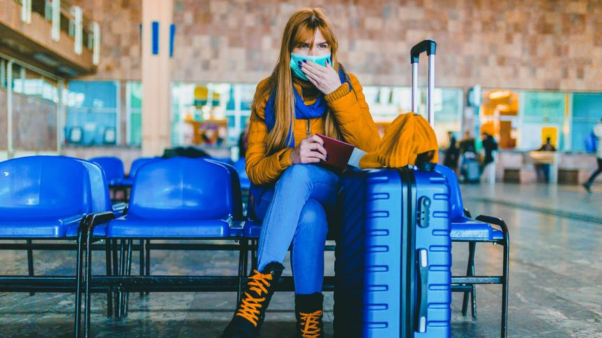 Young woman wearing a protective face mask and waiting for a train at the airport station.