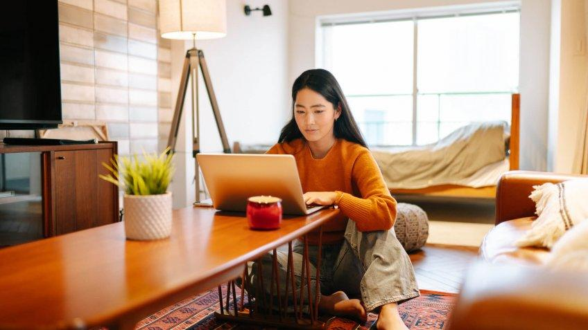 A young woman is using a laptop comfortably in the living room at home.