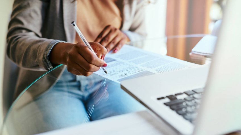 Cropped shot of a woman filling out paperwork at home.