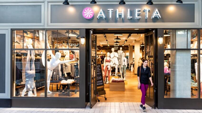 Tysons Corner, USA - January 26, 2018: Athleta store, shop, facade, storefront, door entrance with people, young woman walking in shopping mall in Virginia.