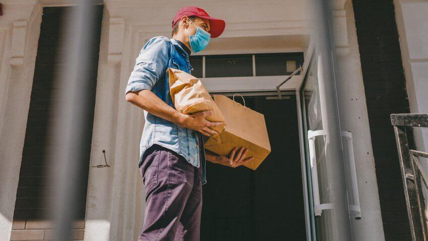 Delivery man holding paper bag with food on white entrance of house background , food delivery man in protective mask.