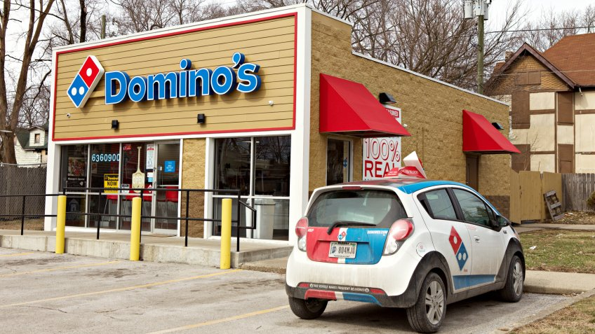 INDIANAPOLIS, IN - FEBRUARY 2019: The front of a Dominos pizza store with a small delivery car in front of the store.
