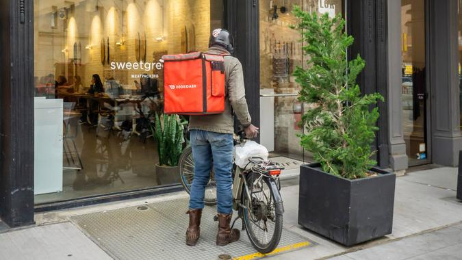 New York NY/USA-October 28, 2018 A DoorDash delivery person outside of a branch of the Sweetgreen restaurant chain in the Meatpacking District in New York.