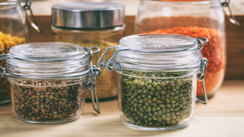 Glass jars with legumes on a table.