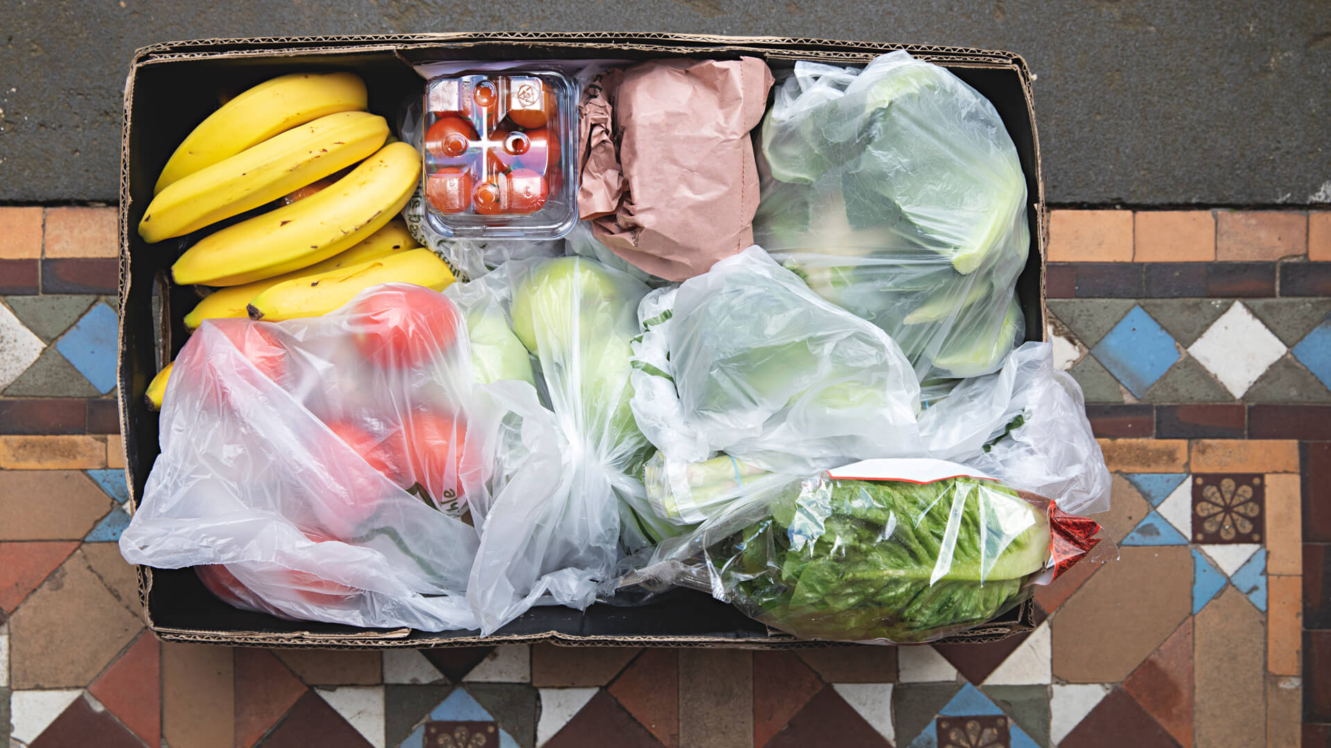 Overhead view of a box of fruit and vegetables is hand delivered and left on the doorstep.