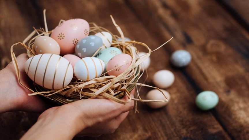 Hands holding stylish easter eggs.