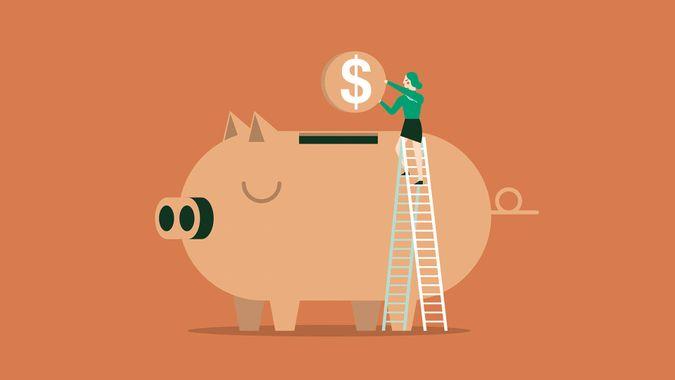 Businesswoman putting coin into a piggy bank.