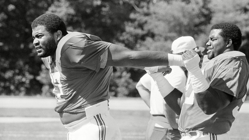 Mandatory Credit: Photo by Mike Kullen/AP/Shutterstock (6559220a)New England Patriots' Kenneth Sims of the University of Texas, the top pick in the National Football League draft, warms up, with an assist from Charles Cook, as the Patriots started training camp with the first workout for rookies and selected veterans at Bryant College in Smithfield, R.