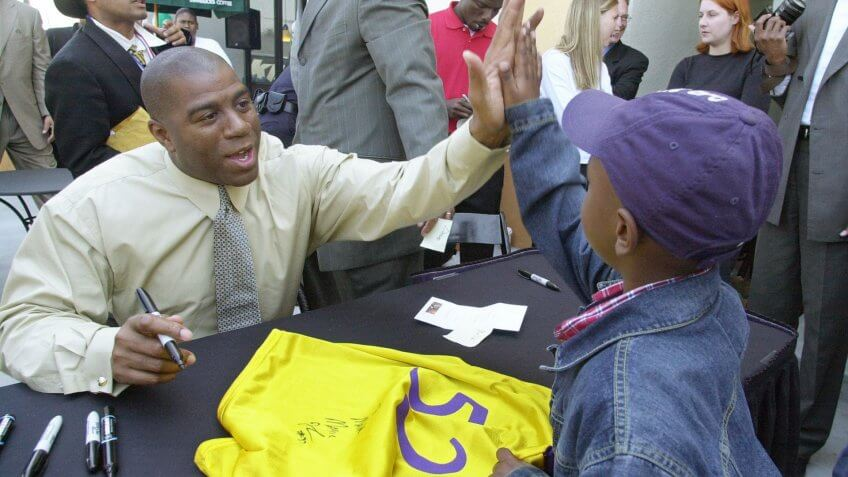 "Magic Johnson Former basketball star Earvin ""Magic"" Johnson, left, slaps hands with Malik Ensley, 7, after signing Ensley's basketball jersey during the grand opening of Johnson's Starbucks coffee shop in south Los Angeles, ."