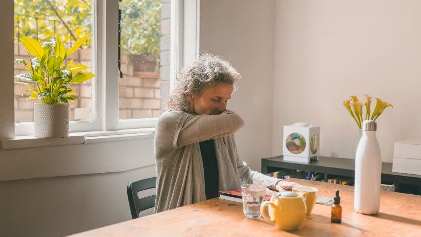 Middle aged woman sitting at table coughing into elbow - coronavirus self isolation concept (selective focus).