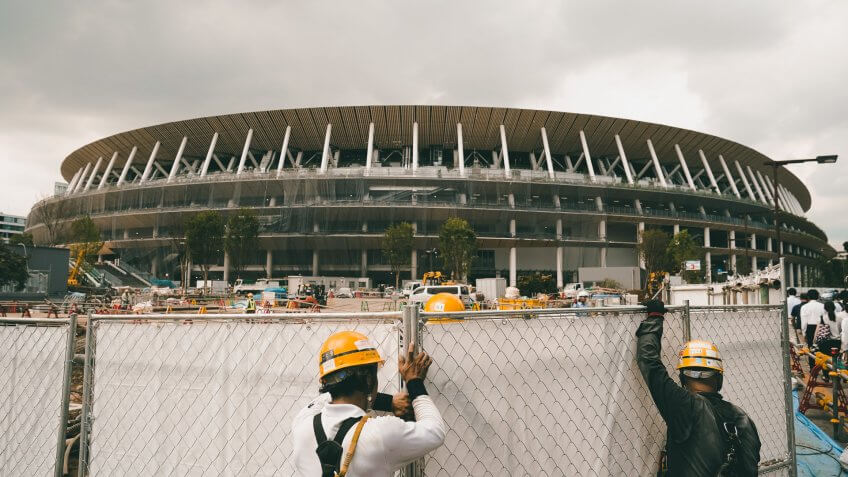 Mandatory Credit: Photo by Jae C Hong/AP/Shutterstock (10434922a)FILE - In this, file, photo, workers adjust fences at the construction site of the New National Stadium, a venue for the opening and closing ceremonies at the Tokyo 2020 Olympics, in Tokyo2020 Labor, Tokyo, Japan - 24 Jul 2019.