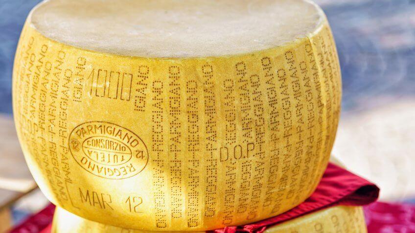Ascona, Switzerland - August 23, 2016: Typical italian Parmigiano Reggiano cheese head on the counter in Ascona street market, Lake Maggiore, Ticino canton, in Switzerland.