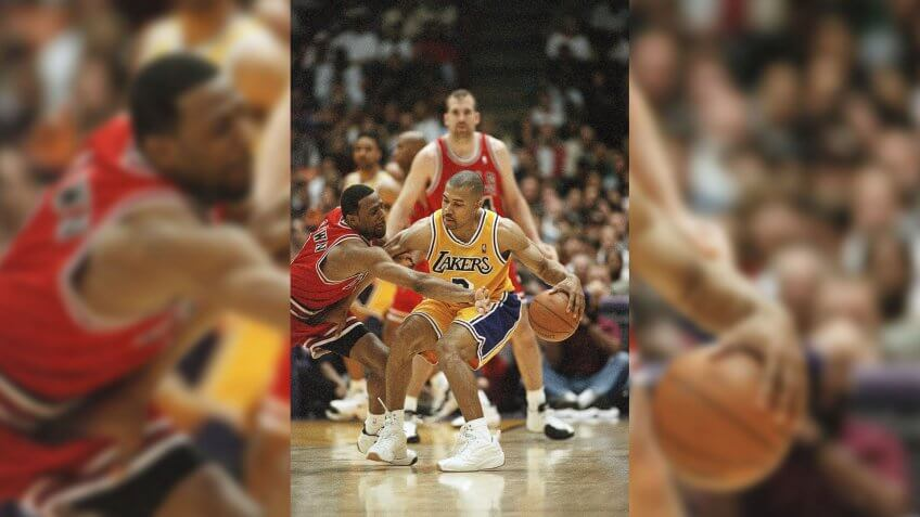 Los Angeles Lakers Derek Fisher, right, who started for injured point guard Nick Van Exel, keeps the ball away from Chicago Bulls Randy Brown during the third quarter, in Inglewood, California.