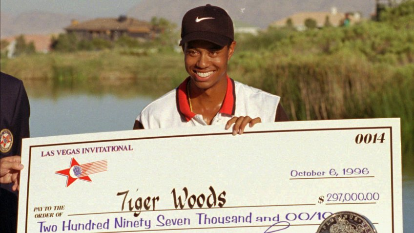 Mandatory Credit: Photo by Lennox Mclendon/AP/Shutterstock (6518354a)WOODS Rookie pro golfer Tiger Woods smiles after receiving a check and trophy for winning the Las Vegas Invitational, at the TPC at Summerlin in Las Vegas.
