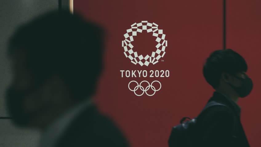 Mandatory Credit: Photo by KIMIMASA MAYAMA/EPA-EFE/Shutterstock (10591296h)Pedestrians wearing masks walk past the emblem of the Tokyo Olympic Games in Tokyo, Japan, 23 March 2020.