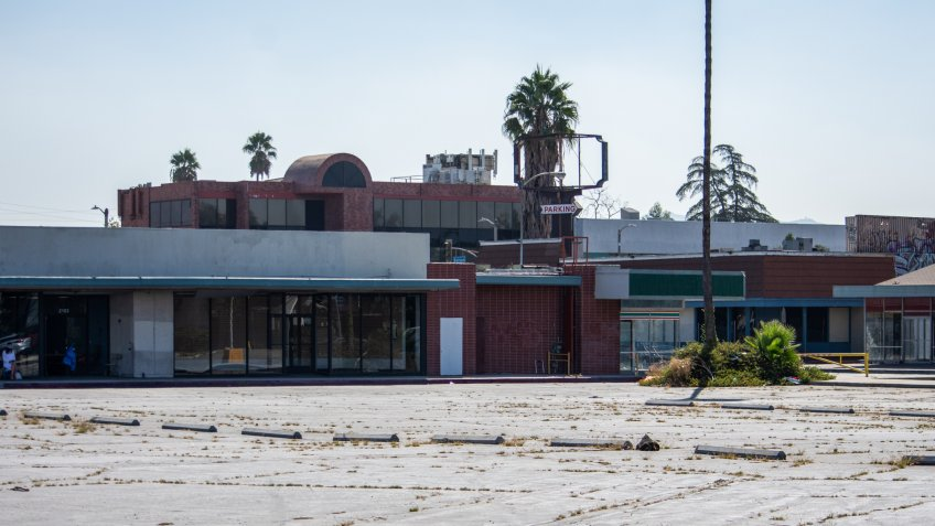 North Hollywood, California / USA - September 18, 2019: Empty parking lot and abandoned storefronts at the historical Valley Plaza shopping center.