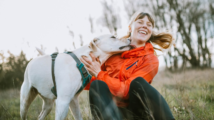 A young adult woman takes a break from exploring a nature park on a beautiful day in the Pacific Northwest, her canine companion joining her.