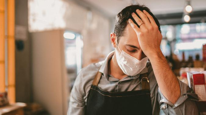 Worried owner with face mask at his small business.