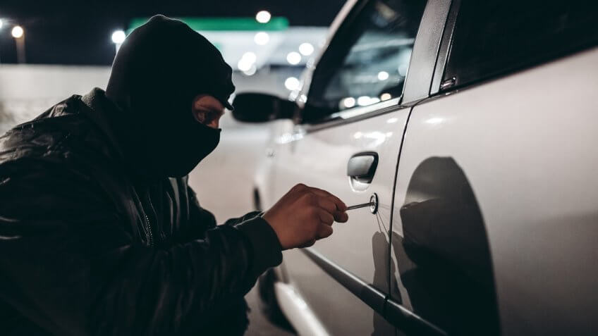 Caucasian man with ski mask stealing a car at night.