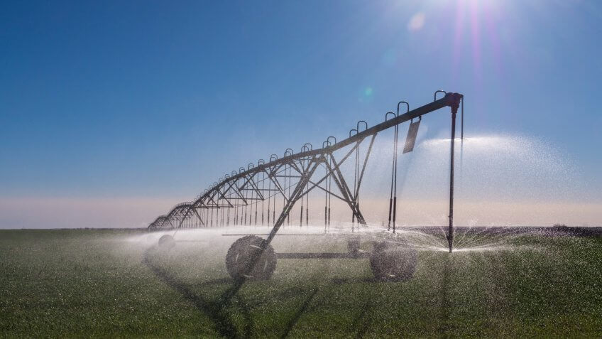 A center-pivot sprinkler irrigates wheat fields in drought-stricken western Kansas in.